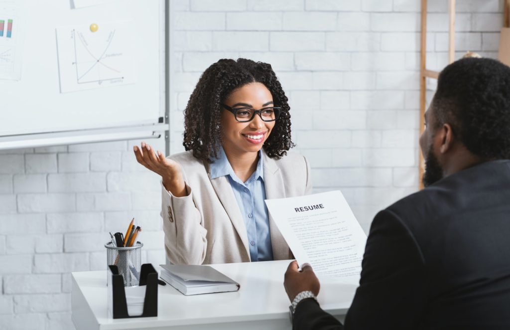 Friendly personnel manager interviewing black candidate during job interview at modern office